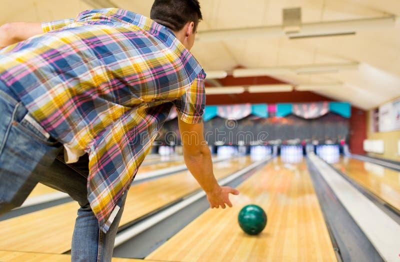Chiuda su della palla di lancio dell'uomo nel club di bowling fotografia stock libera da diritti