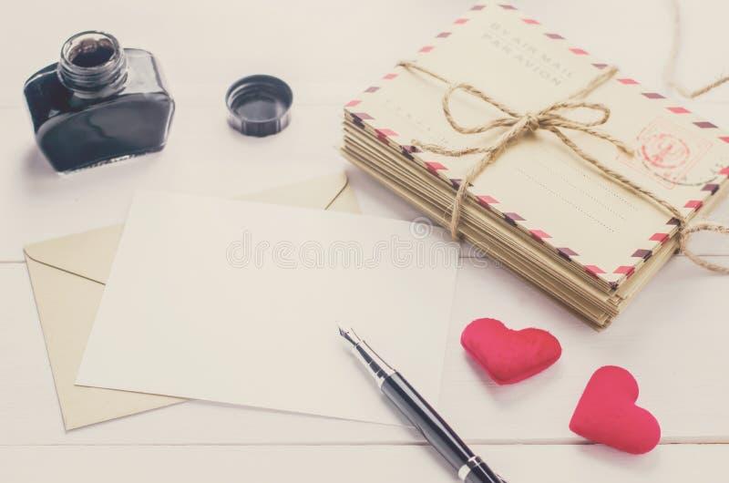 Chiuda su della penna stilografica con la cartolina d'auguri bianca in bianco con vin fotografia stock libera da diritti