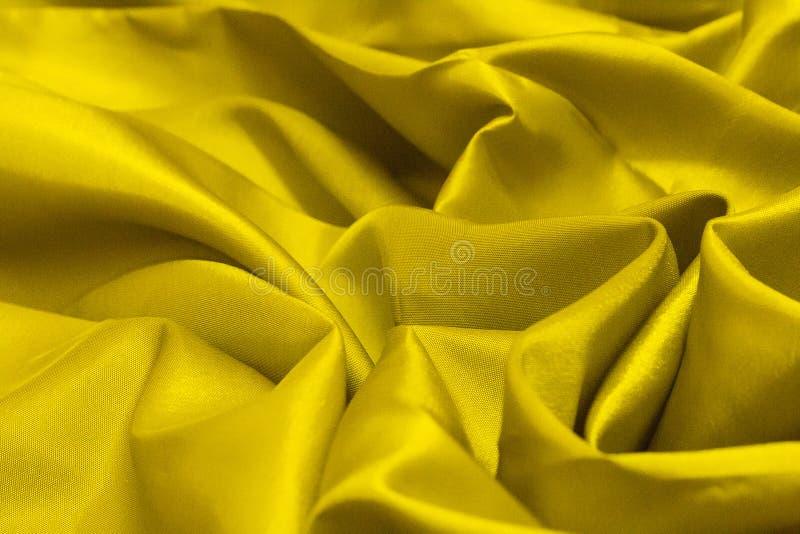 Chiuda su della piega di struttura di tela del tessuto naturale dell'oro per progettazione Tela di sacco strutturata Tela dorata  fotografia stock libera da diritti