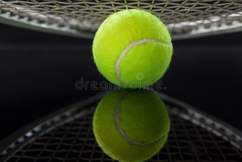 Chiuda su della racchetta sopra pallina da tennis con la riflessione fotografie stock