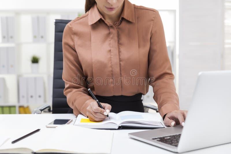 Chiuda su della ragazza nella battitura a macchina marrone della blusa immagini stock