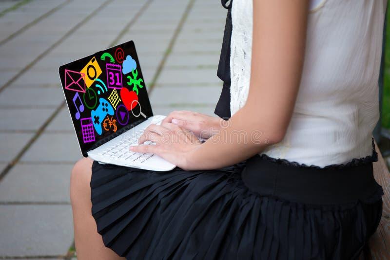 Chiuda su della ragazza in uniforme scolastico facendo uso del computer portatile con le icone di media immagine stock