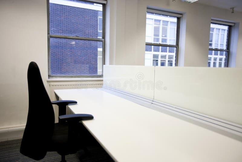 Chiuda su della sedia dell'ufficio e dello scrittorio vuoto dalla finestra fotografia stock