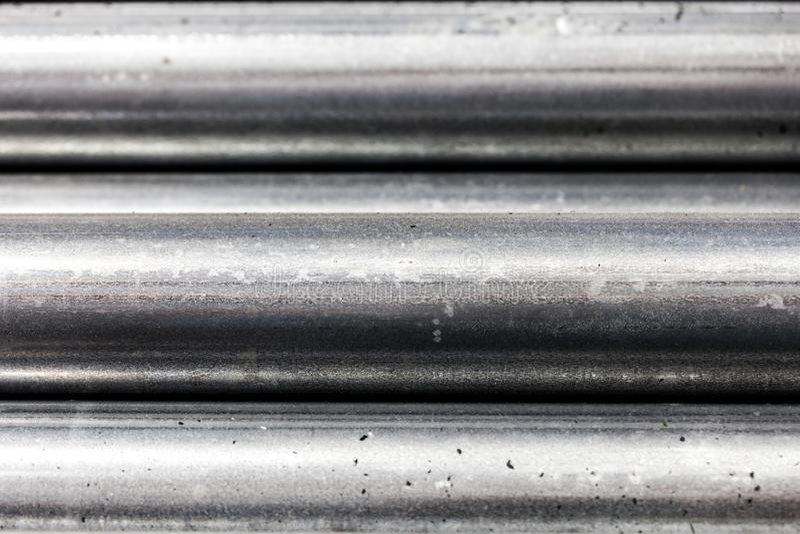 Chiuda su della sezione dei tubi d'acciaio impilati sopra a vicenda/ha strutturato il fondo metallico immagine stock libera da diritti