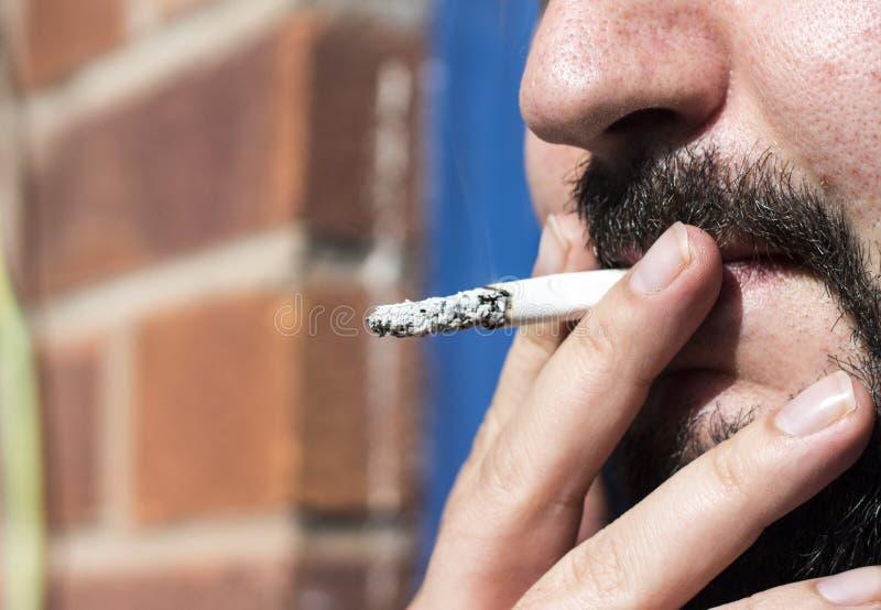 Chiuda su della sigaretta di fumo dell'uomo fotografia stock libera da diritti