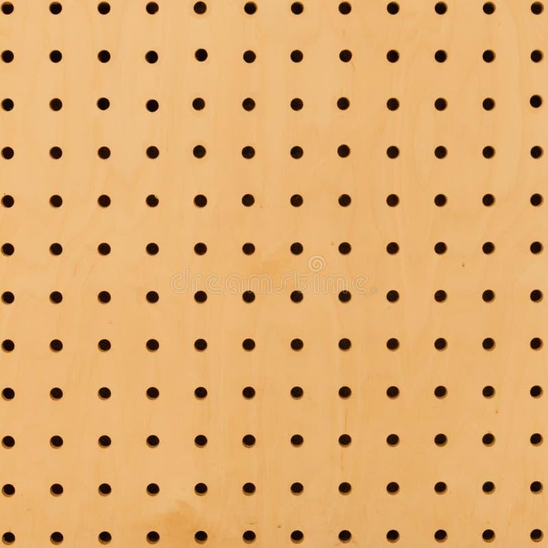 Chiuda su della superficie gialla marrone della parete ha forato la struttura di griglia Modello di punto fotografia stock libera da diritti