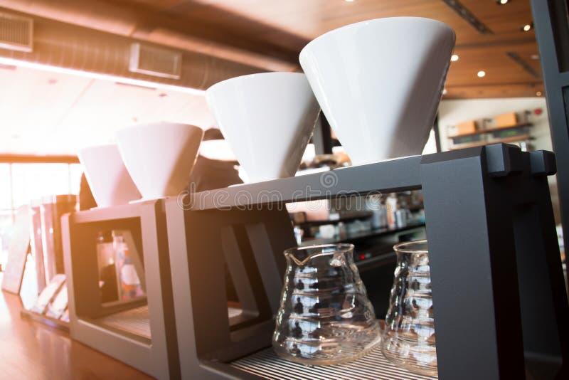 Chiuda su della tazza del gocciolamento del caffè in caffè con luce solare fotografia stock libera da diritti