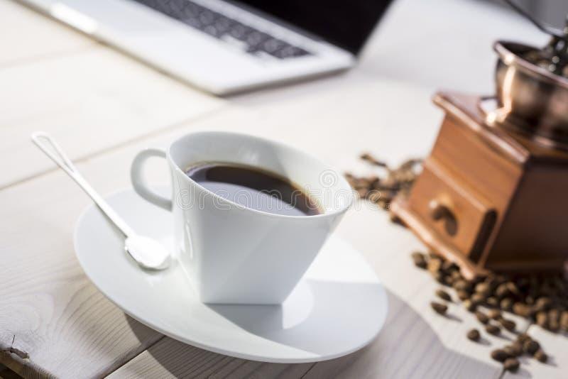 Chiuda su della tazza di caffè sulla tavola con la smerigliatrice e un computer portatile fotografie stock