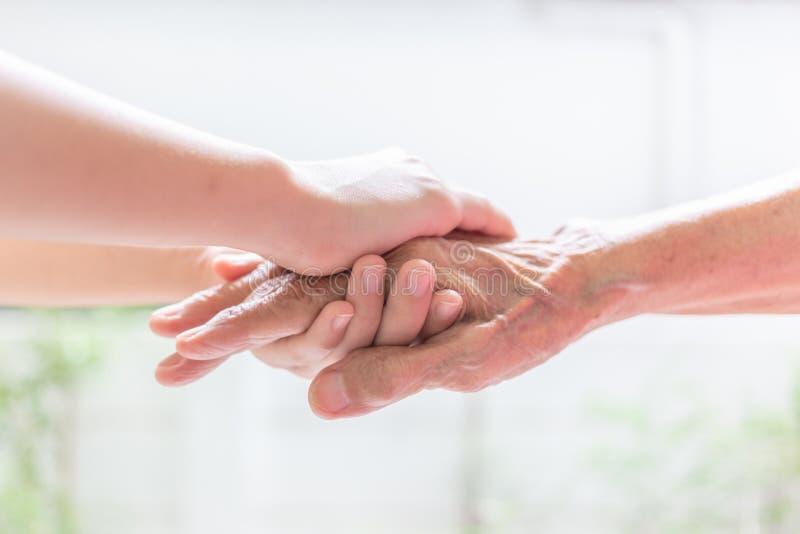 Chiuda su della tenuta della mano della giovane donna con la tenerezza gli anziani immagini stock libere da diritti