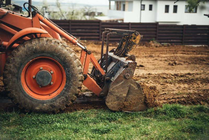 Chiuda su della terra commovente del mestolo del bulldozer e di fare abbellendo gli impianti fotografia stock