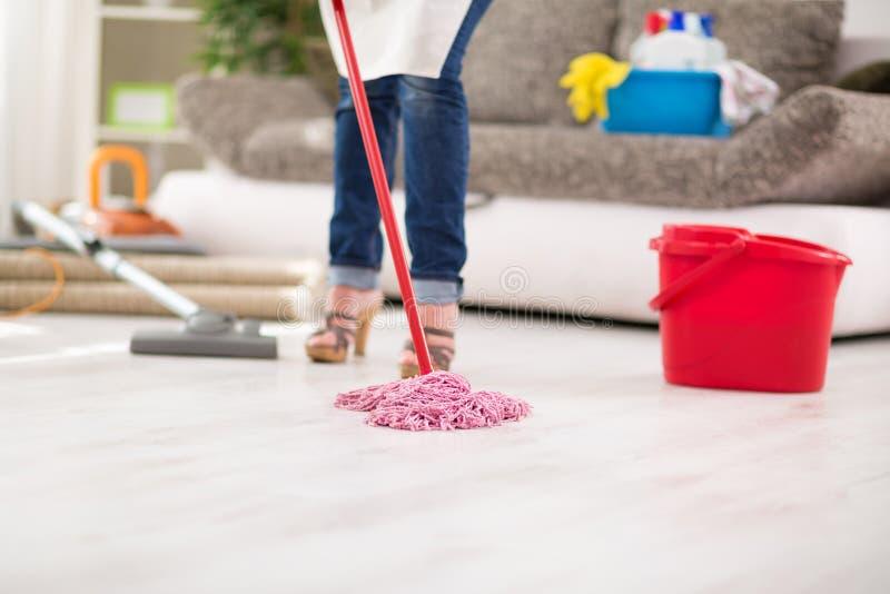 Chiuda su della zazzera, casalinga con la zazzera pulisce il pavimento fotografia stock