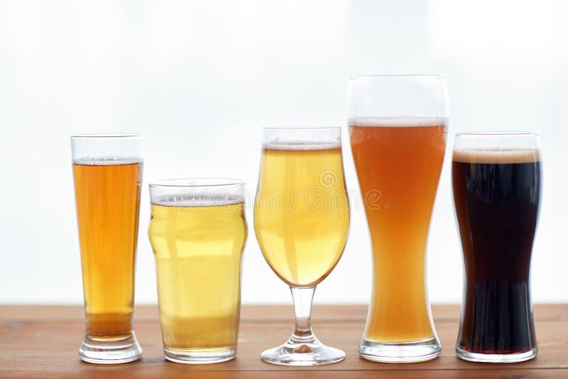 Chiuda su delle birre differenti in vetri sulla tavola fotografia stock