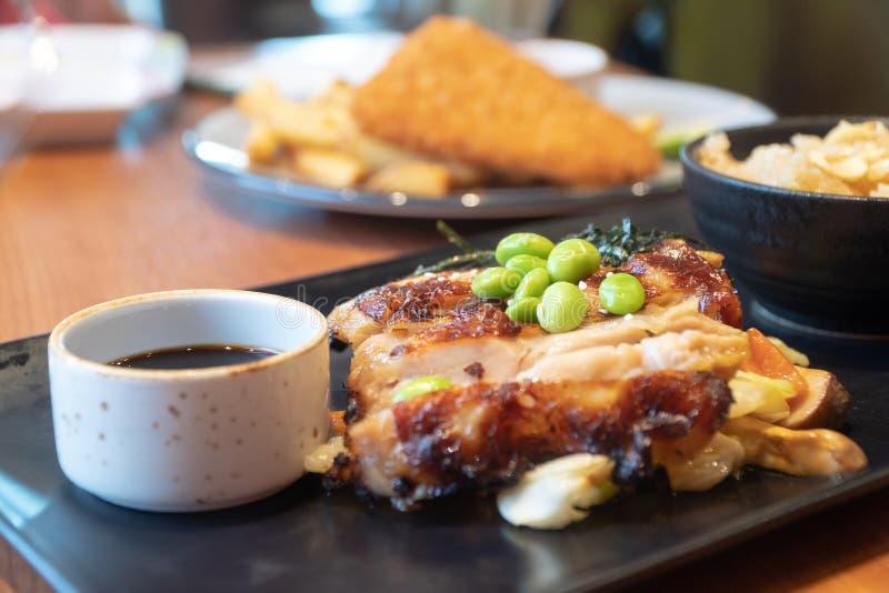 Chiuda su delle bistecche del pollo con la tazza di salsa sulla banda nera Piselli ed alga giapponese sulle bistecche del pollo c immagini stock