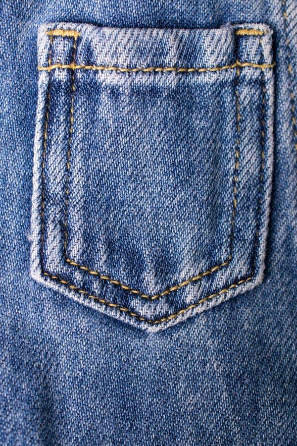 Chiuda su delle blue jeans intascano Struttura delle blue jeans fotografia stock