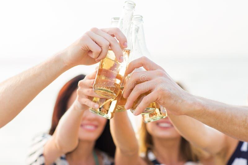 Chiuda su delle bottiglie tintinnanti degli amici con le bevande fotografia stock libera da diritti