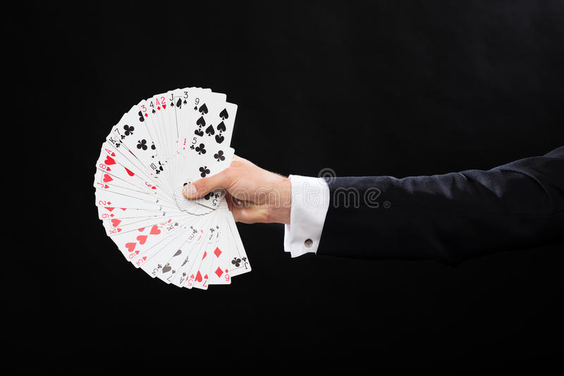 Chiuda su delle carte da gioco della tenuta della mano del mago immagini stock libere da diritti