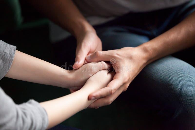 Chiuda su delle coppie che si tengono per mano, dando il supporto psicologico c fotografie stock