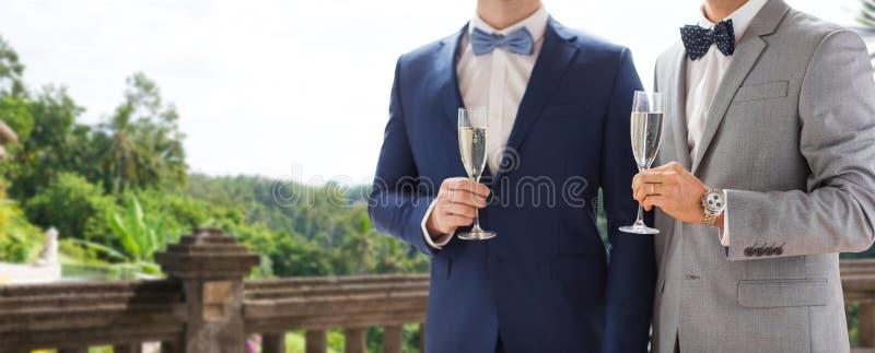 Chiuda su delle coppie gay maschii con i vetri del champagne fotografia stock