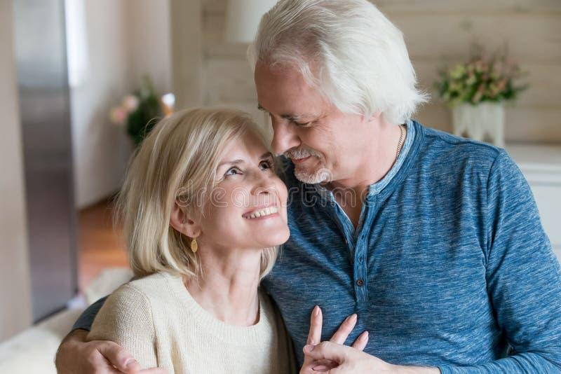 Chiuda su delle coppie invecchiate medie nell'amore fotografia stock