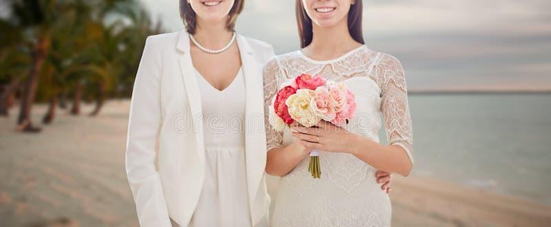 Chiuda su delle coppie lesbiche felici con i fiori fotografia stock libera da diritti