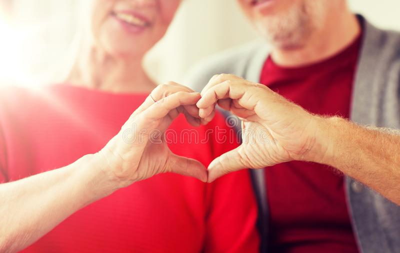 Chiuda su delle coppie senior che mostrano il segno del cuore della mano fotografie stock libere da diritti