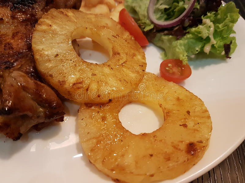 Chiuda su delle fette dell'ananas come piatto laterale decorativo per i piatti hawaiani di stile immagini stock