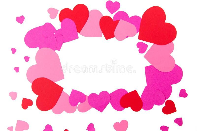 Chiuda su delle forme rosse e rosa del cuore nel telaio fotografie stock