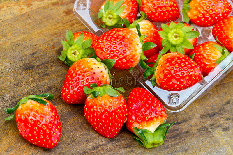 Chiuda su delle fragole fresche sulla tavola e sulla plastica b dell'interno fotografia stock