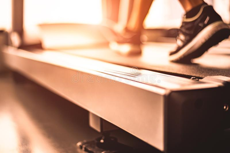 Chiuda su delle gambe della donna che pareggiano sulla pedana mobile con gli abiti sportivi e le scarpe da tennis Concetto di all fotografie stock