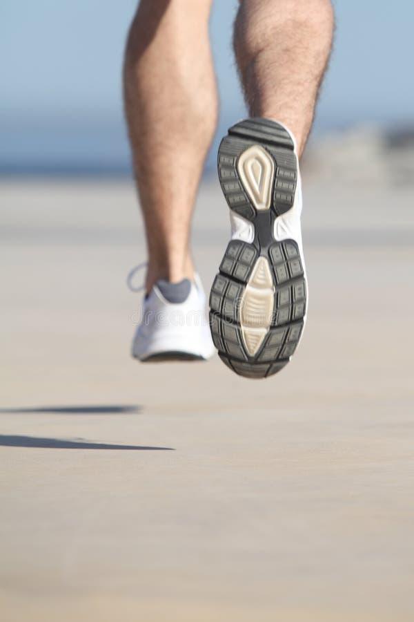 Chiuda su delle gambe unfocused di un uomo che corrono sul calcestruzzo di un lungonmare fotografie stock libere da diritti