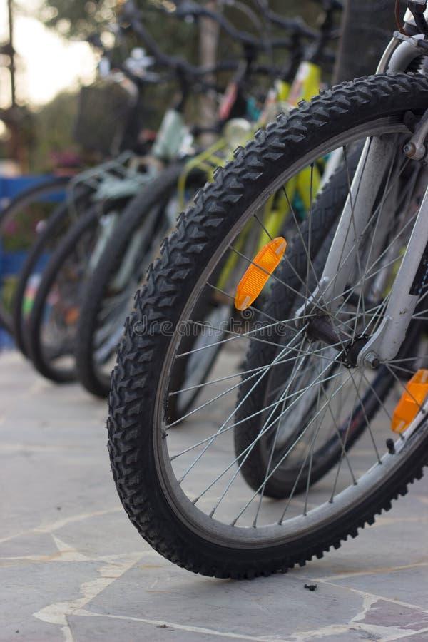 Chiuda su delle gomme di una bicicletta su un punto di parcheggio della bicicletta immagine stock libera da diritti