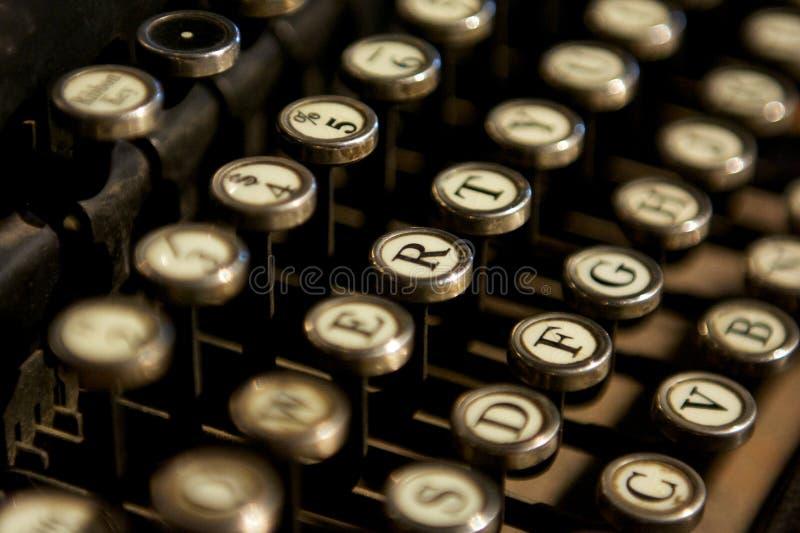 Chiuda su delle lettere e numera le chiavi di una macchina da scrivere d'annata immagine stock
