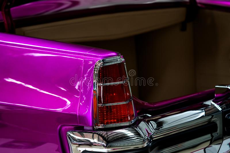 Chiuda su delle luci della coda e dello stivale dell'automobile classica metallica rosa immagine stock