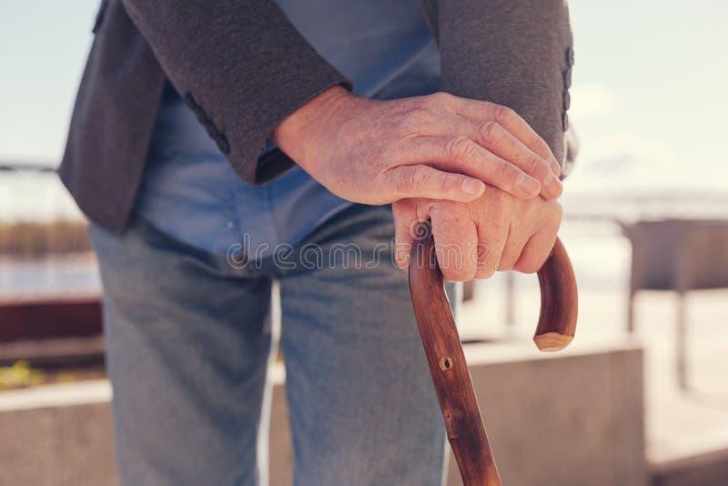 Chiuda su delle mani anziane dei maschi su una canna immagini stock libere da diritti