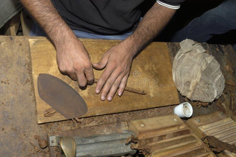 Chiuda su delle mani che fanno un sigaro dalle foglie del tabacco fotografia stock