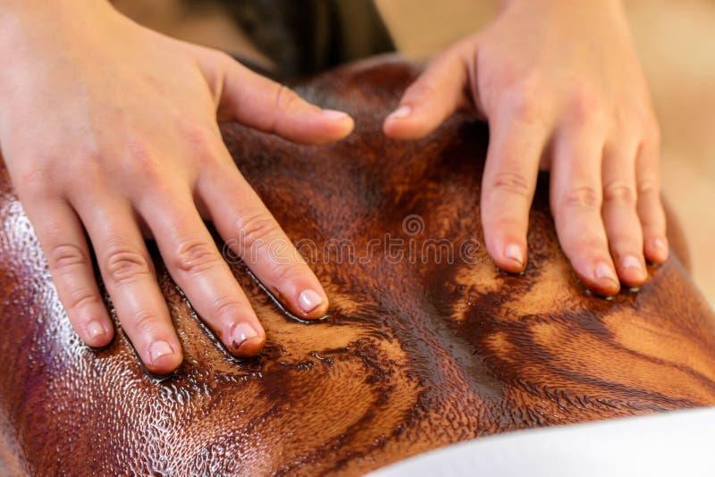 Chiuda su delle mani che spandono la cioccolata calda sulla parte posteriore femminile fotografia stock libera da diritti