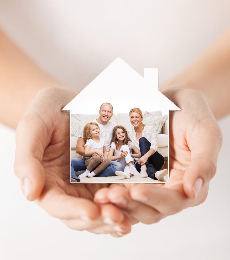Chiuda su delle mani che tengono la forma della casa con la famiglia fotografie stock libere da diritti
