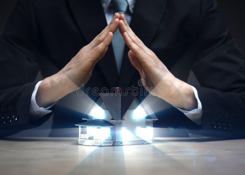 Chiuda su delle mani come tetto sopra il modello della casa fotografia stock libera da diritti