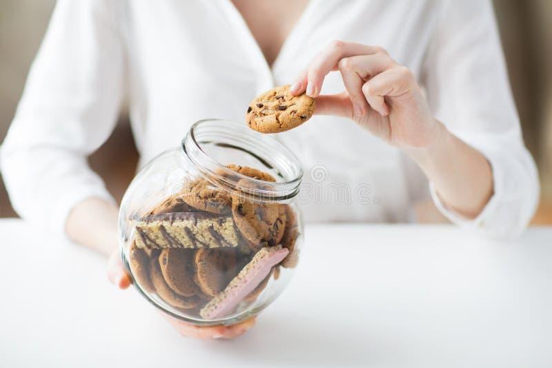 Chiuda su delle mani con i biscotti del cioccolato in barattolo immagini stock
