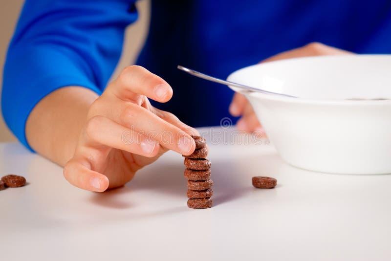 Chiuda su delle mani dei bambini che mangiano i cereali per la prima colazione o il pranzo fotografie stock libere da diritti