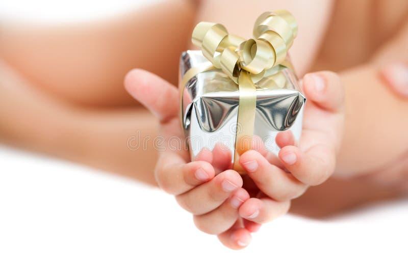 Chiuda in su delle mani dei bambini che tengono il presente. fotografie stock libere da diritti