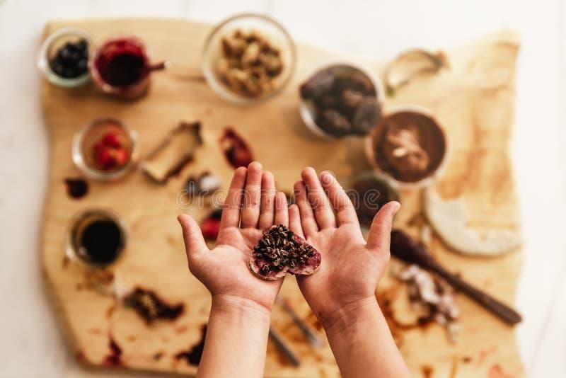 Chiuda su delle mani del bambino che preparano i biscotti di cottura immagini stock