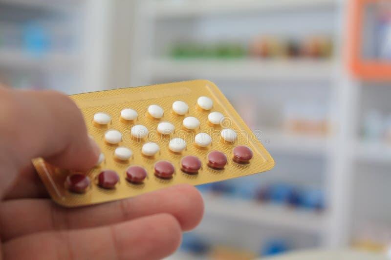 Chiuda su delle mani del farmacista che tengono le pillole anticoncezionali fotografia stock libera da diritti