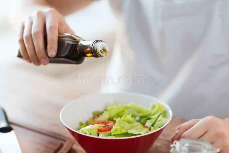 Chiuda su delle mani del maschio che condiscono l'insalata in una ciotola immagine stock