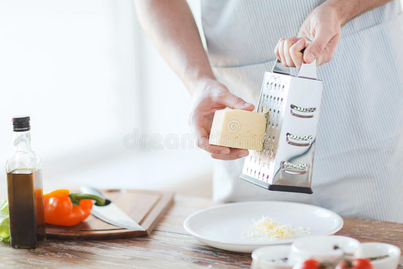 Chiuda su delle mani del maschio che grattano il formaggio immagine stock libera da diritti