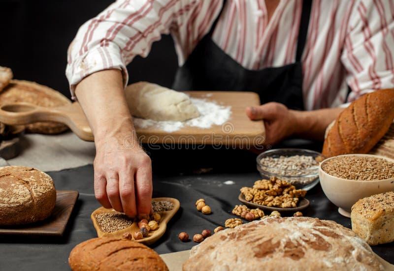 Chiuda su delle mani del panettiere che impastano la pasta e che producono il pane con un matterello fotografie stock libere da diritti