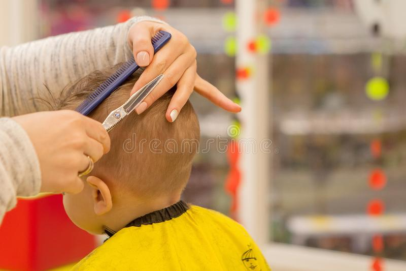 Chiuda su delle mani del parrucchiere La donna ? stante e facente il taglio di capelli per il bambino piccolo Sta tenendo un pett fotografia stock