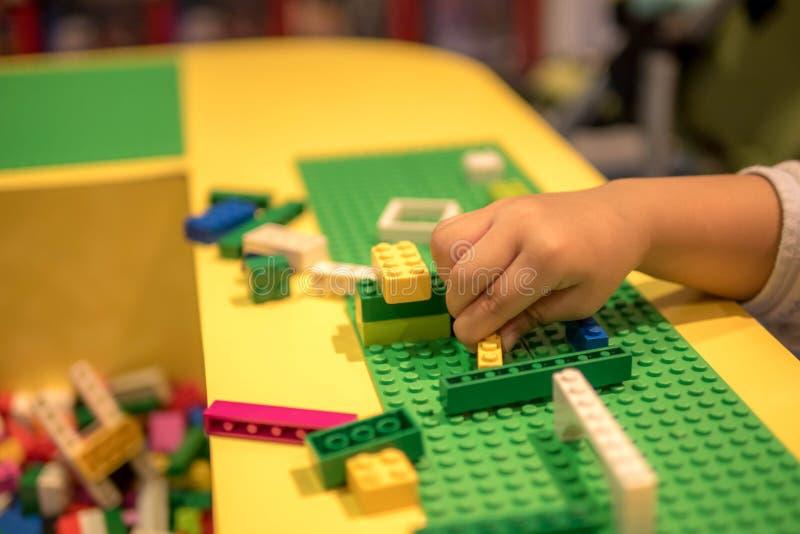 Chiuda su delle mani del ` s del bambino che giocano con i mattoni di plastica variopinti alla tavola Presto imparando Priorità b fotografie stock