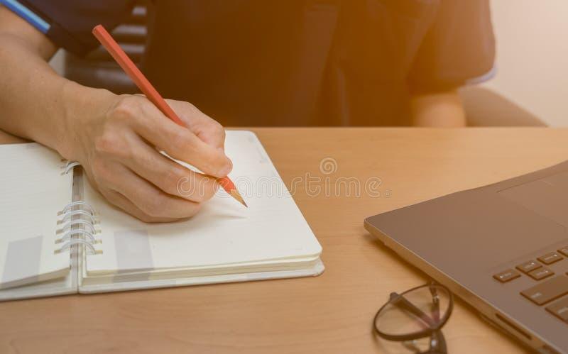 Chiuda su delle mani dell'uomo che scrivono sul blocco note e sul lavoro immagini stock