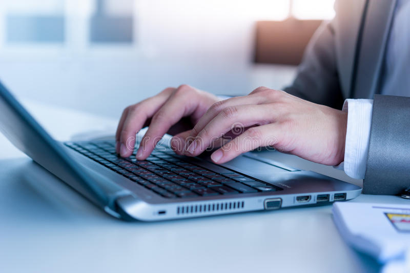 Chiuda su delle mani dell'uomo di affari che scrivono sul computer portatile immagini stock libere da diritti